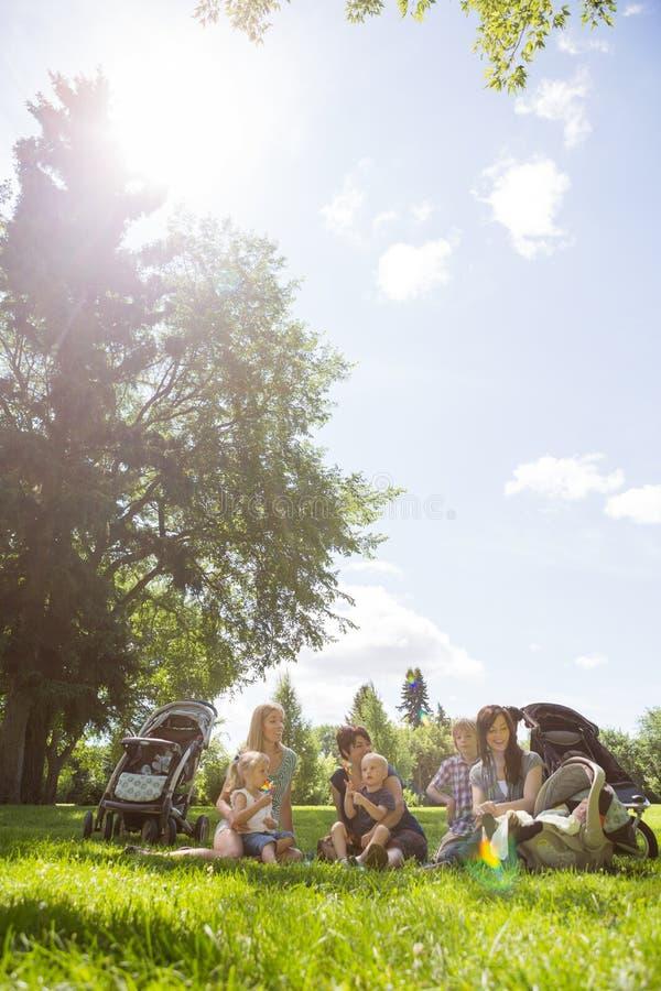 Mères et enfants passant le temps de qualité en parc photographie stock libre de droits