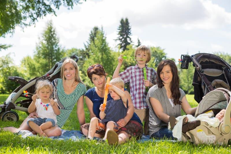 Mères heureuses et enfants appréciant le pique-nique photo stock