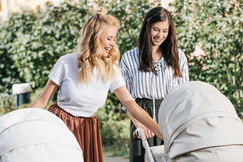 mères heureuses regardant des voitures d'enfant photographie stock