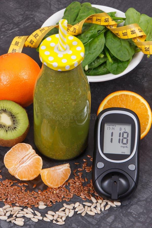 Mètre de glucose avec le niveau de sucre, le ruban métrique et le coctail fraîchement mélangé des fruits et légumes, du diabète e image libre de droits