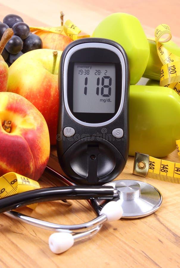 Mètre de glucose avec le stéthoscope, les fruits et les haltères médicaux pour l'usage dans la forme physique image stock