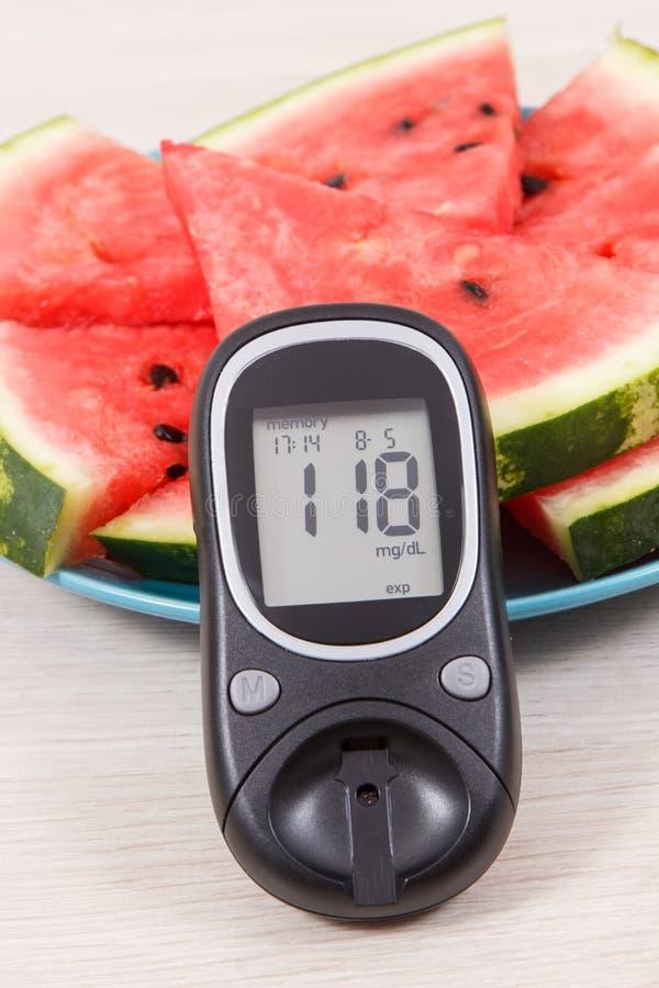 Mètre de glucose pour le niveau de mesure de sucre et pastèque contenant les minerais naturels, le diabète et le concept sain de  images stock
