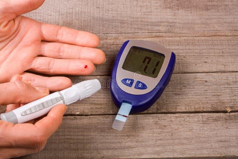 Mètre de glucose sanguin avec une main sur un vieux fond en bois photos stock
