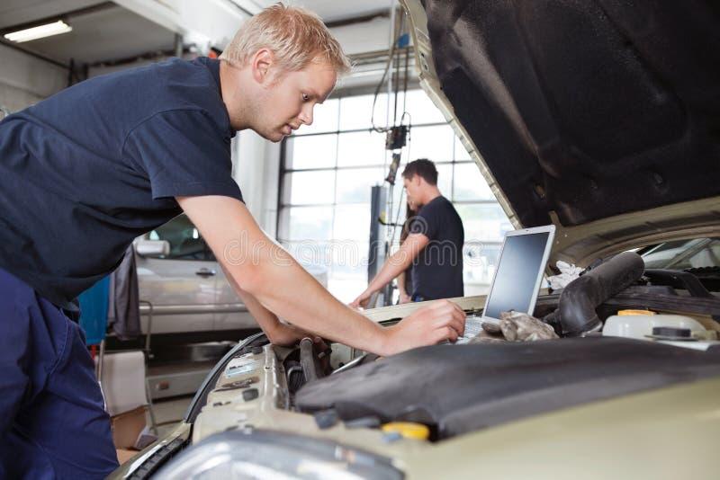 Mécanicien à l'aide de l'ordinateur portatif tout en travaillant au véhicule images stock