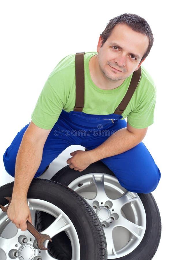 Mécanicien amical avec des pneus de voiture photo stock