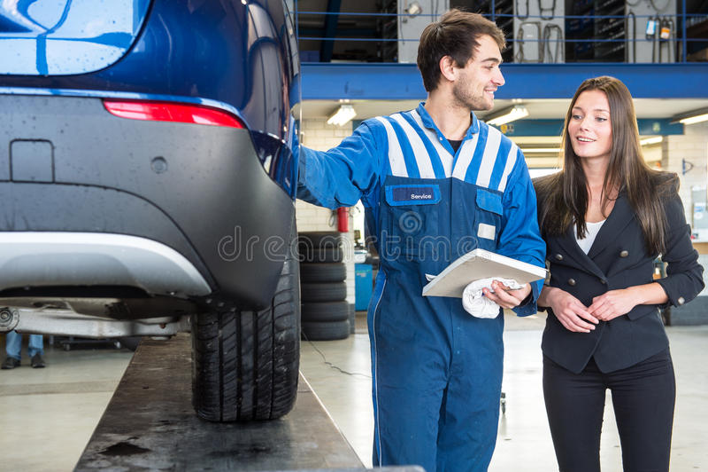 Mécanicien amical, montrant à un service client son travail photos stock