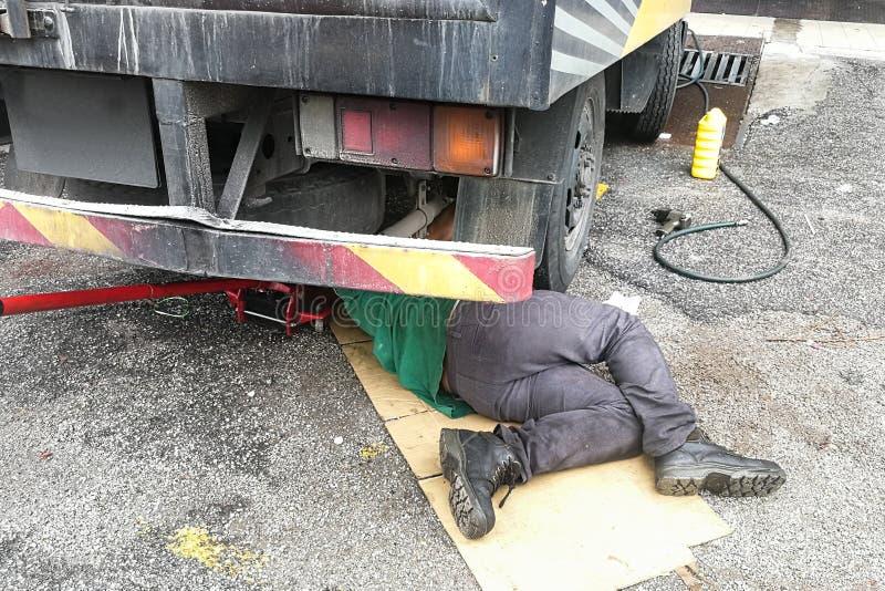 Mécanicien asiatique sous le camion réparant le moteur gras sale avec des RP images stock