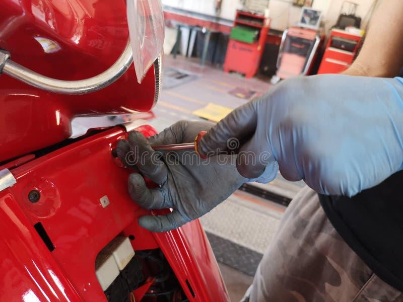 Mécanicien au travail sur le scooter photo stock