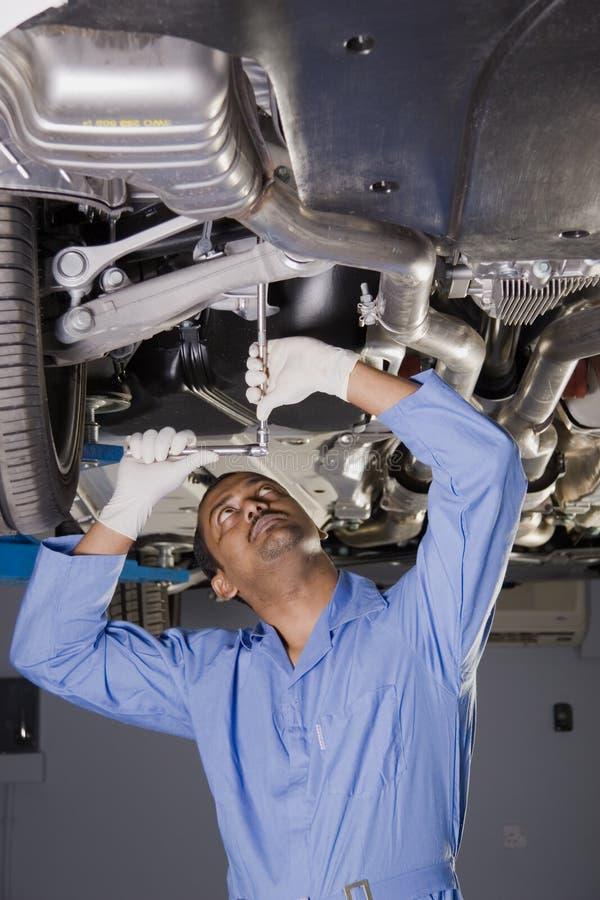 Mécanicien automatique sous le véhicule photographie stock