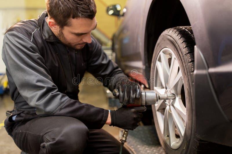 Mécanicien automobile avec le pneu de voiture changeant de tournevis photos stock
