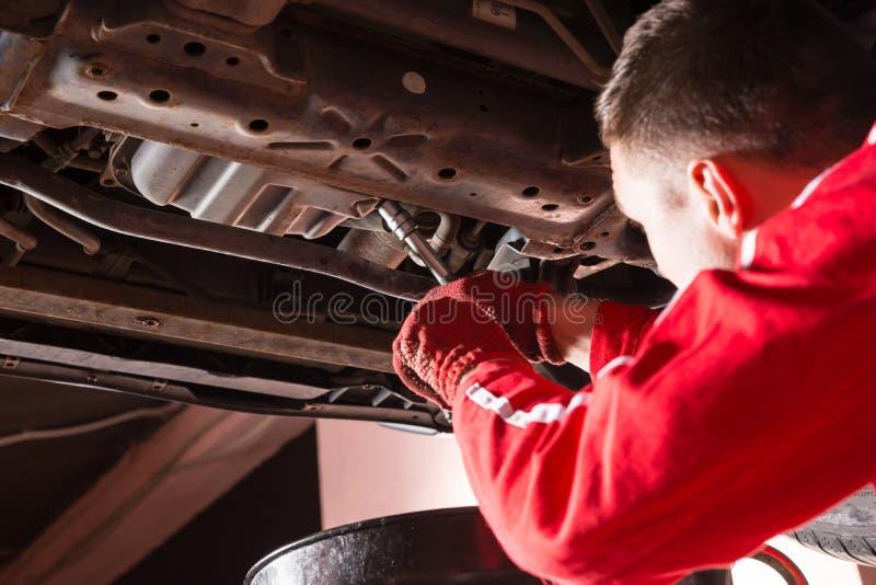 Mécanicien automobile dans l'uniforme fonctionnant sous une voiture et un cha soulevés images libres de droits