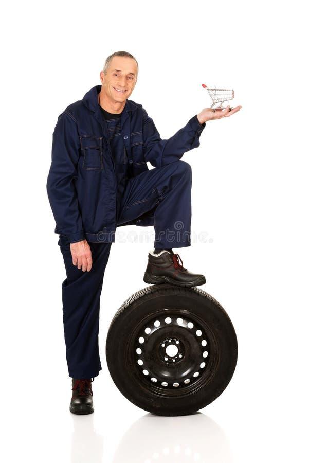 Mécanicien avec un pneu et un panier photographie stock libre de droits