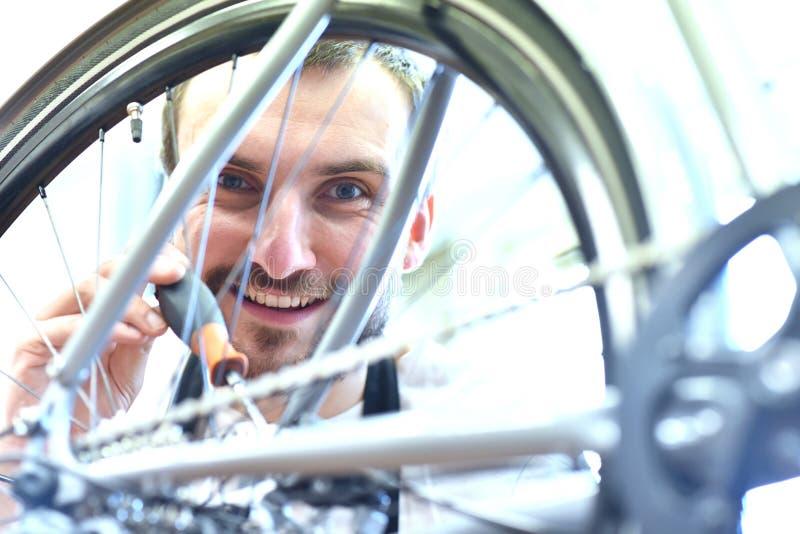 Mécanicien dans un atelier de réparations de bicyclette huilant la chaîne d'un vélo photos stock