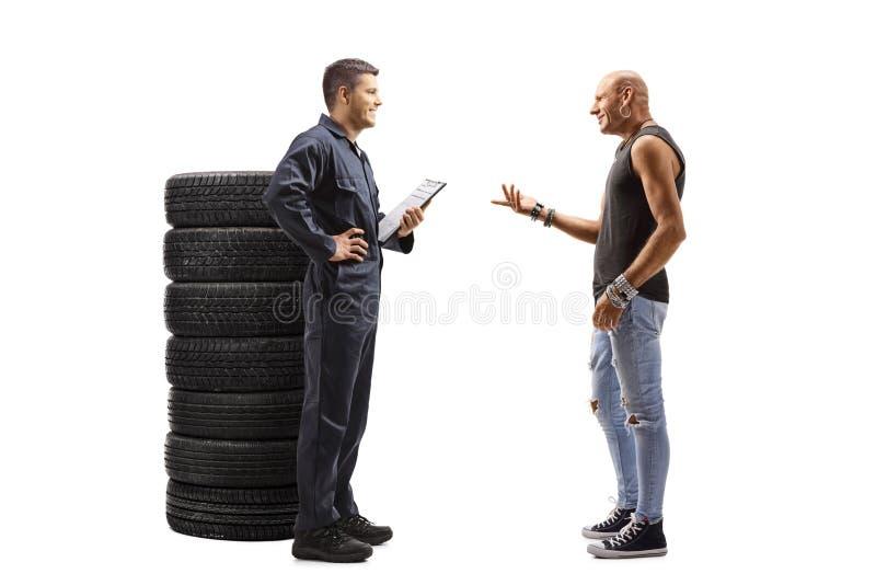 Mécanicien de l'automobile et un client masculin parlant images stock