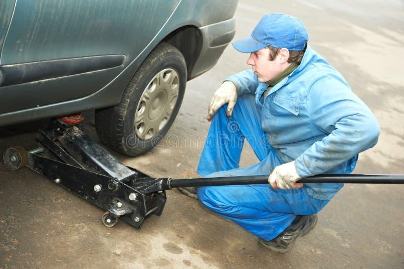 Mécanicien de Machanic à l'ajustage de précision de pneu avec le plot de véhicule image libre de droits