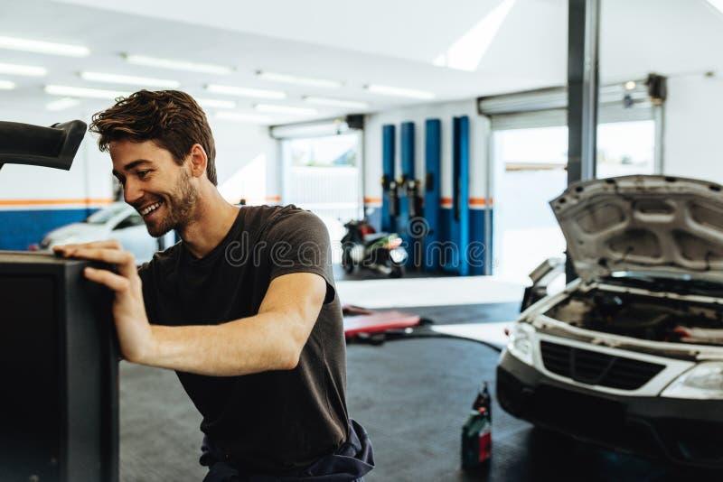 Mécanicien de sourire faisant le diagnostic de voiture sur l'ordinateur photos stock