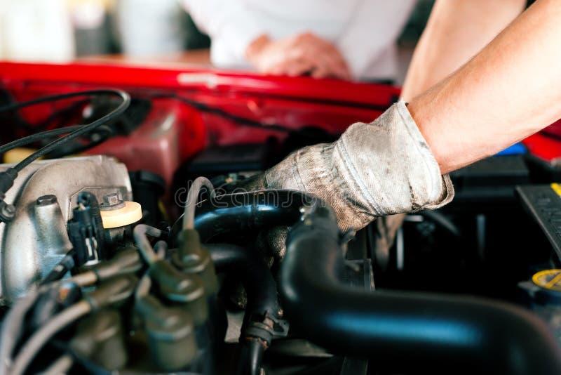 Mécanicien de véhicule dans l'atelier de réparations photo stock