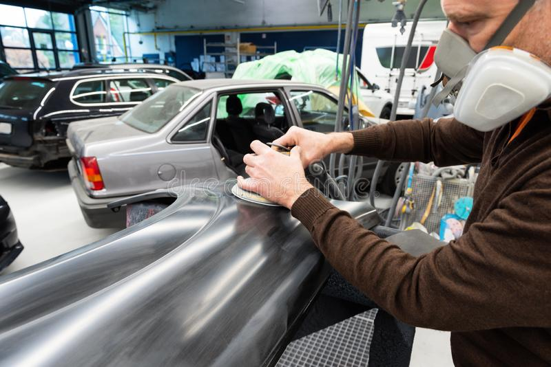 Mécanicien de voiture avec des morcellements de masque de poussière par pièce de voiture dans une station service - atelier de ré image libre de droits