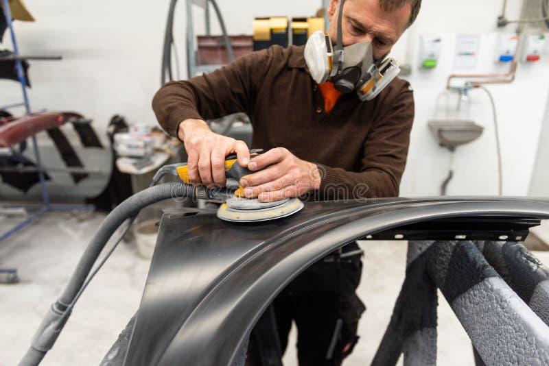 Mécanicien de voiture avec des morcellements de masque de poussière par pièce de voiture dans une station service - atelier de ré photos stock