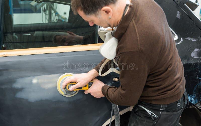 Mécanicien de voiture avec des morcellements de masque de poussière par pièce de voiture dans une station service - atelier de ré photos libres de droits