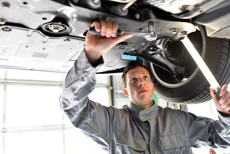 Mécanicien de voiture dans un atelier - réparation et diagnostic de moteur sur le VE images libres de droits