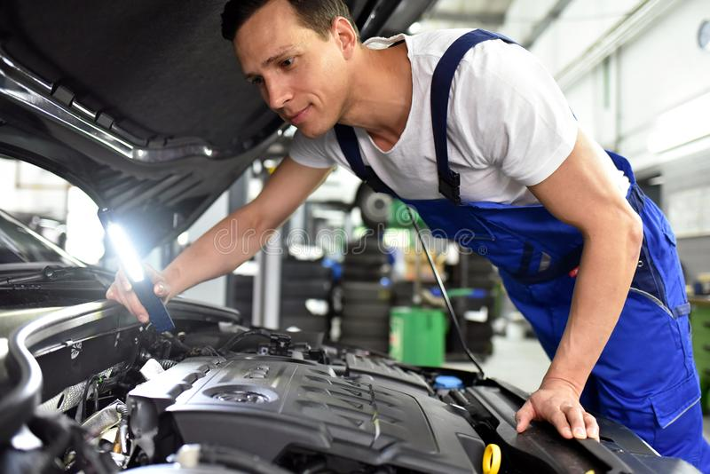 Mécanicien de voiture dans un atelier - réparation et diagnostic de moteur sur le VE images stock
