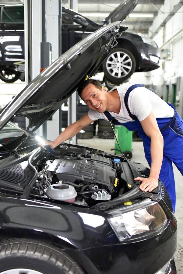 Mécanicien de voiture dans un atelier - réparation et diagnostic de moteur sur le VE photo libre de droits