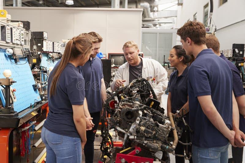 Mécanicien de voiture montrant des moteurs aux apprentis image stock