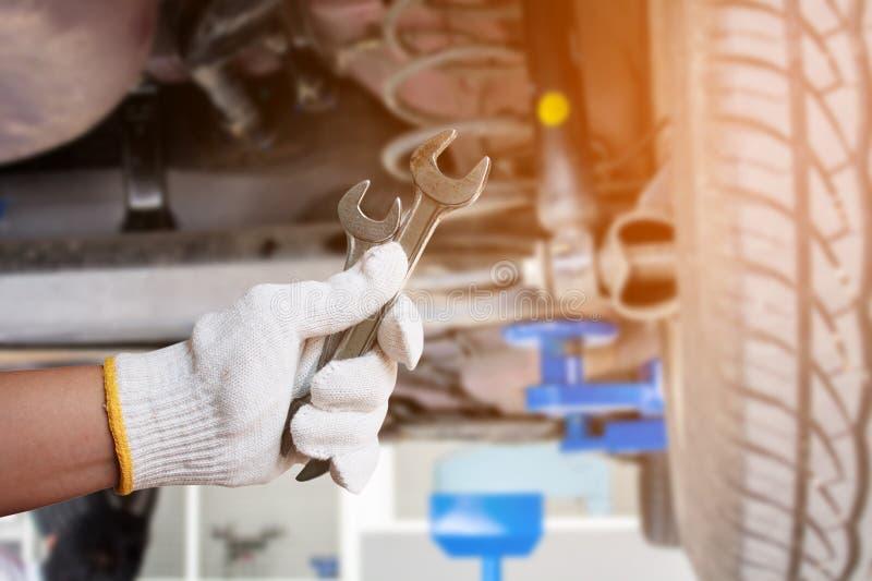 Mécanicien de voiture tenant la clé au garage de réparation de voiture photographie stock libre de droits