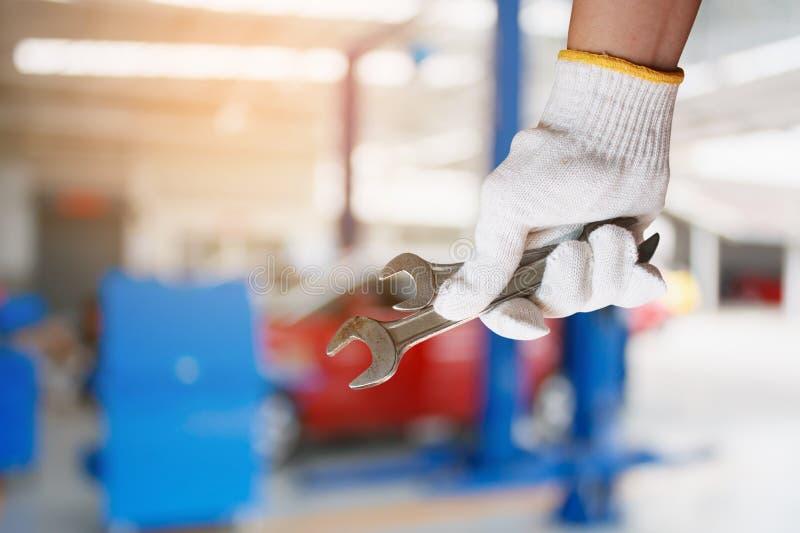 Mécanicien de voiture tenant la clé au garage de réparation de voiture photos stock