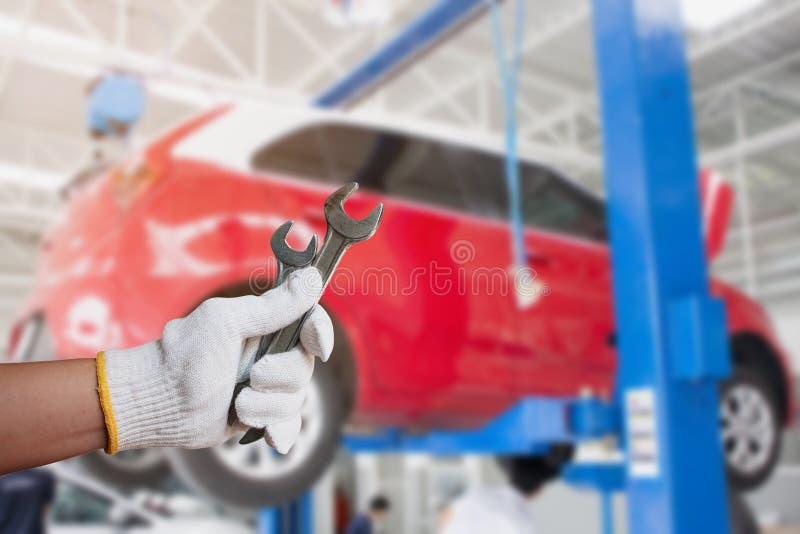 Mécanicien de voiture tenant la clé au garage de réparation de voiture image libre de droits