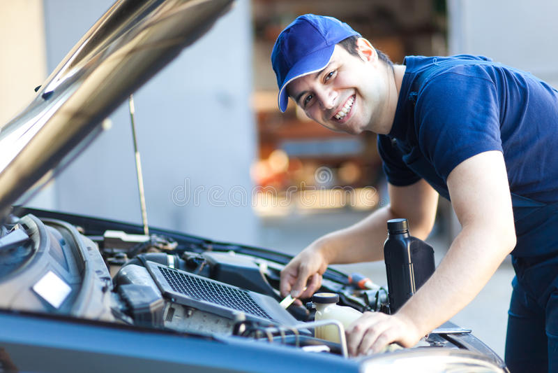 Mécanicien de voiture travaillant dans le service des réparations automatique images stock