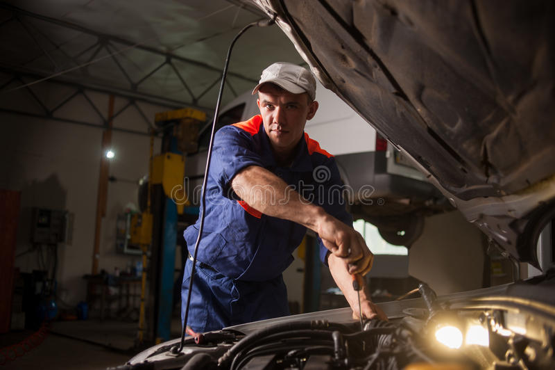 Mécanicien de voiture travaillant dans le service des réparations automatique Réparation de la voiture utilisant photographie stock