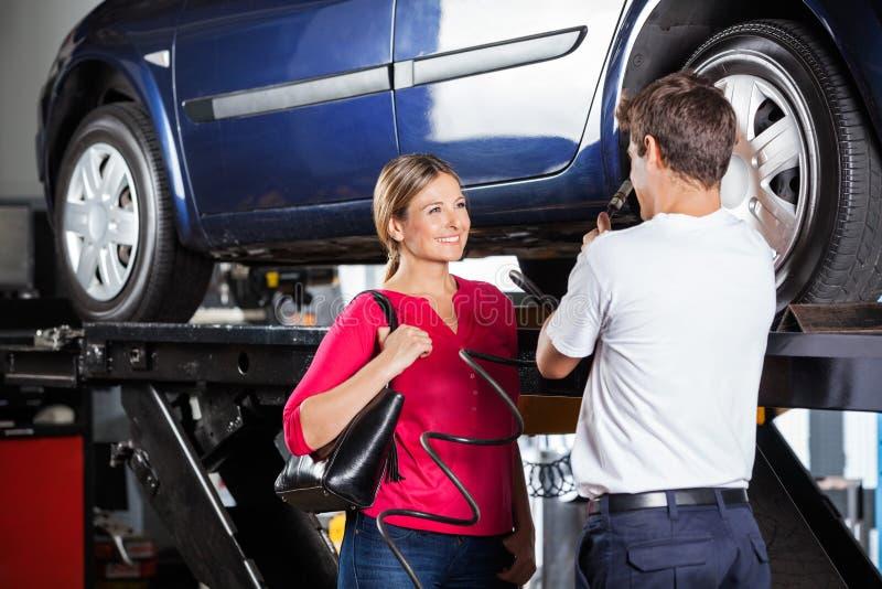Mécanicien Discussing With Customer tout en remplissant photographie stock