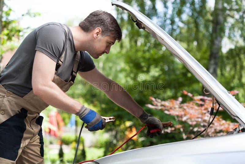 Mécanicien employant des câbles de pullover pour mettre en marche une batterie de voiture photos stock