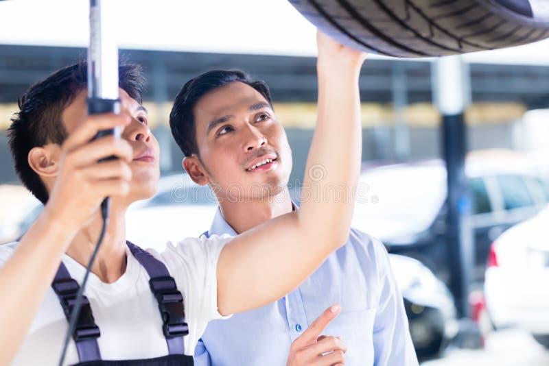 Mécanicien et client de voiture dans l'atelier automatique asiatique photos stock