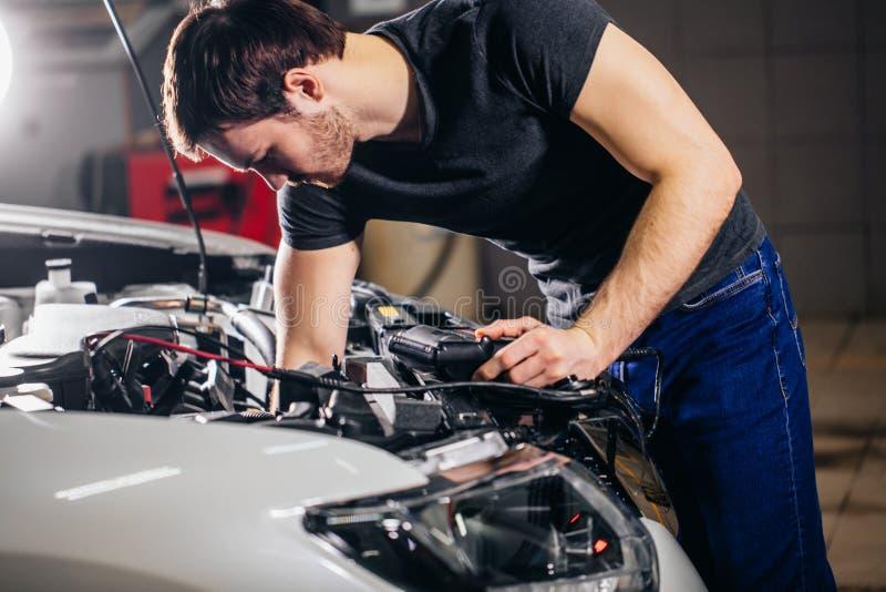 Mécanicien examinant le système électrique sur l'automobile photo libre de droits