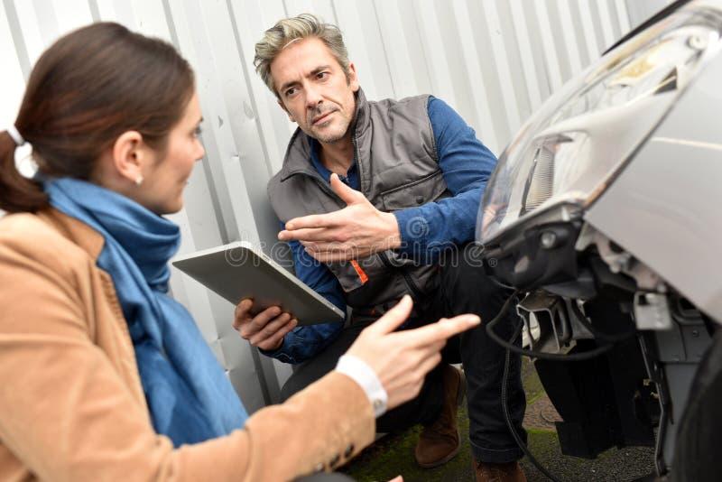 Mécanicien expliquant au client quelles réparations doivent être faites photographie stock libre de droits