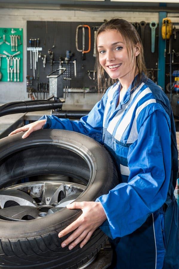 Mécanicien féminin de sourire Mounting Car Tire sur Rim In Garage photos libres de droits