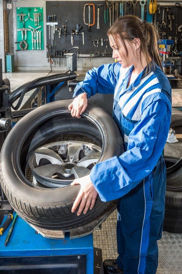 Mécanicien féminin Mounting Car Tire sur Rim In Garage photographie stock libre de droits