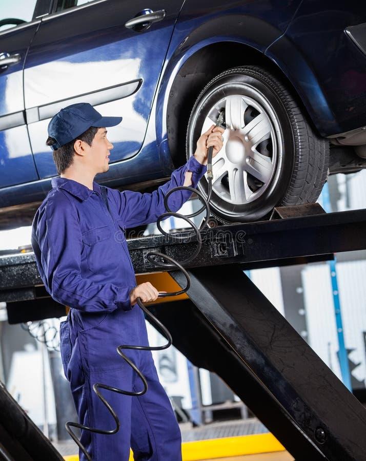 Mécanicien Inflating Car Tire au garage photo stock