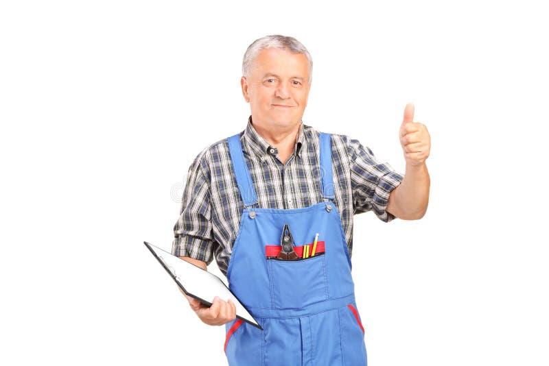Mécanicien masculin tenant le presse-papiers et renonçant au pouce image stock