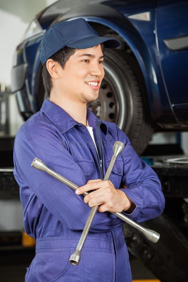 Mécanicien réfléchi Holding Rim Wrench At Garage photos stock