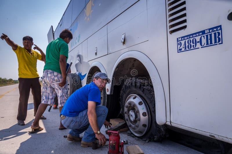 Mécanicien réparant le pneu crevé à la panne d'autobus photographie stock