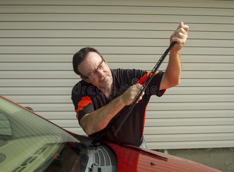Mécanicien Replacing Wiper Blades sur une voiture photo libre de droits