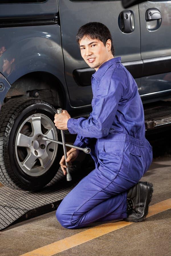 Mécanicien sûr Fixing Car Tire au garage photographie stock libre de droits