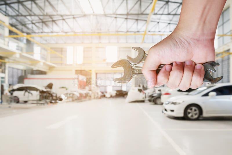 mécanicien tenant la clé sur le centre de service des réparations de voiture photo libre de droits