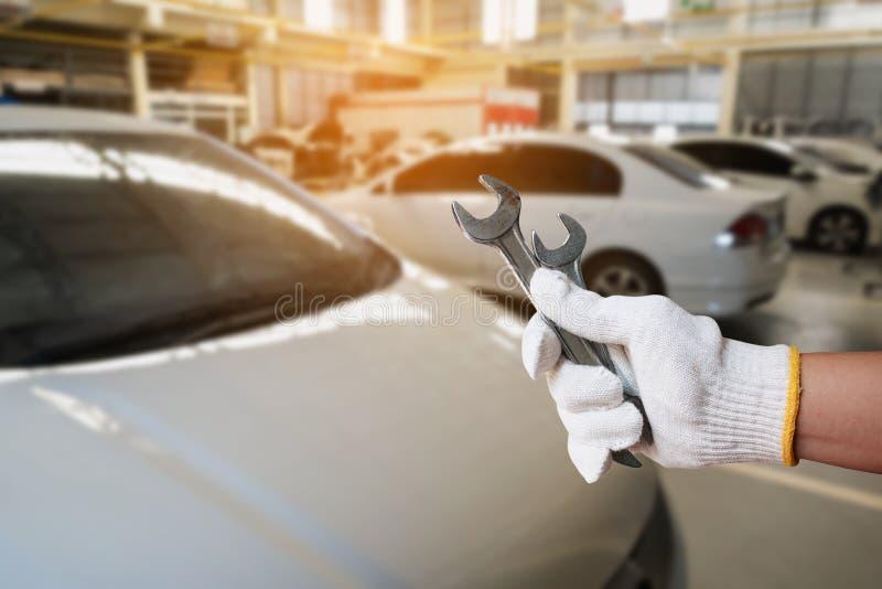 mécanicien tenant la clé sur le centre de service des réparations de voiture image libre de droits