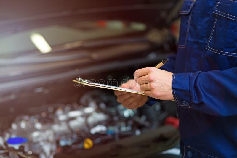 Mécanicien travaillant au moteur de voiture dans l'atelier de réparations automatiques photos libres de droits