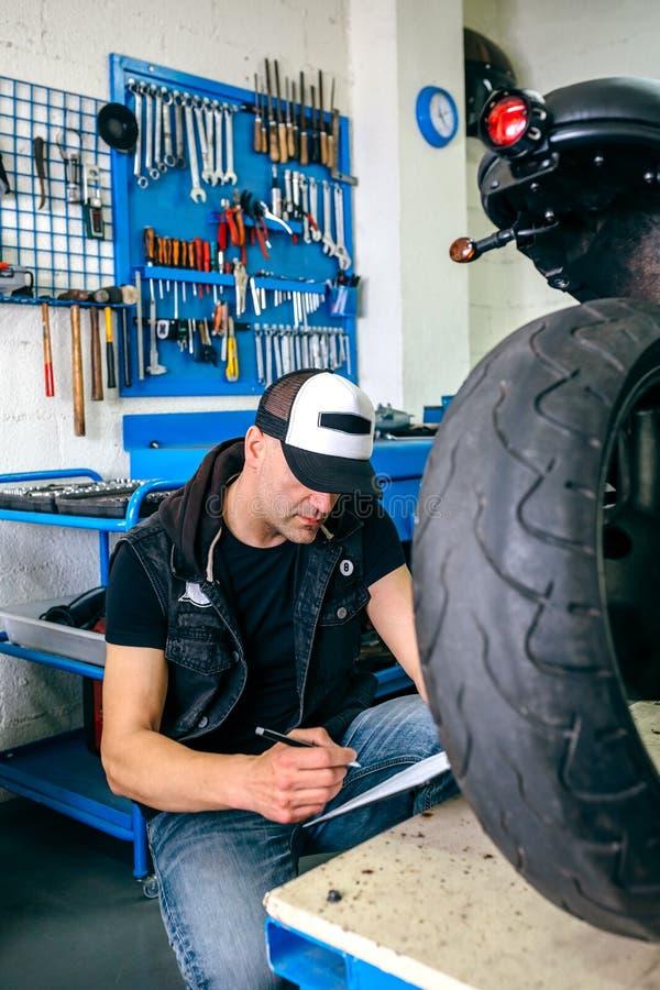 Mécanicien vérifiant la moto photographie stock